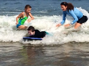 Caitlin and Jen teaching Rio to boogie board in the waves of Ocean Park, Maine. Photo Credit: Juliette Woolf