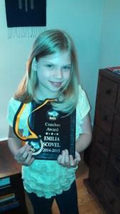 Emilia proudly holds up her Coaches Award. Photo Credit: G. Scovel